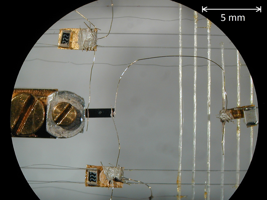 Figure 3: The setup used for thermal conductivity measurements in which high resolution thermometers and a heat source are thermally anchored to a single crystal sample.  One end of the sample is tightly coupled to an external heat bath, from which the thermometers and heater are simultaneously decoupled.